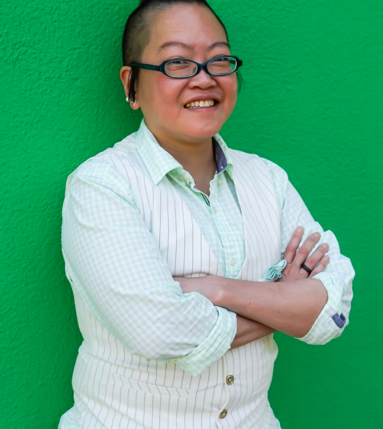 Photo of Prof. Steph Tai standing in front of green background.