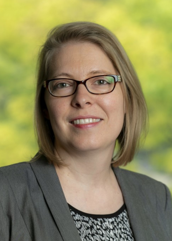 Photo of Associate Dean Bonnie Shucha, in grey suit in front of green leafy background.